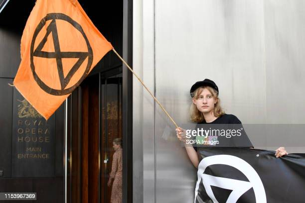 An Extinction Rebellion activist holds a flag and a banner outside the Royal Opera House main entrance during a protest in London Environmental...