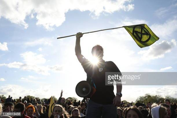 An Extinction Rebellion campaigner waves a flag at the closing ceremony in Hyde Park to mark the voluntary end of the London protests on April 25...