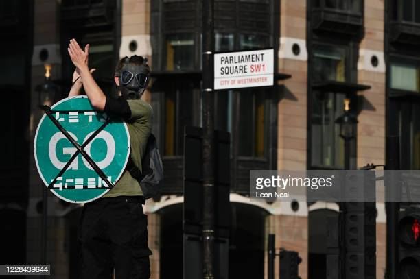 An Extinction Rebellion demonstrator climbs on top of a car as traffic comes to a stop in Parliament Square on September 10, 2020 in London, England....