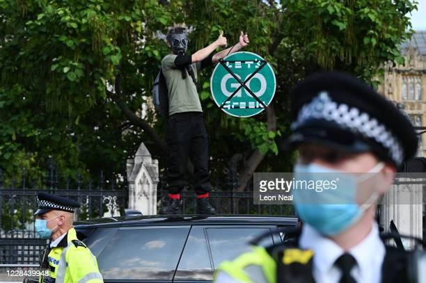 An Extinction Rebellion demonstrator climbs on top of a car as traffic comes to a stop in Parliament Square on September 10 2020 in London England...