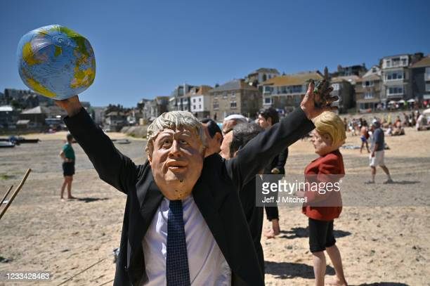 An Extinction Rebellion environmental activist wearing a Boris Johnson mask stages a demonstration during the G7 summit on June 13, 2021 in St Ives,...