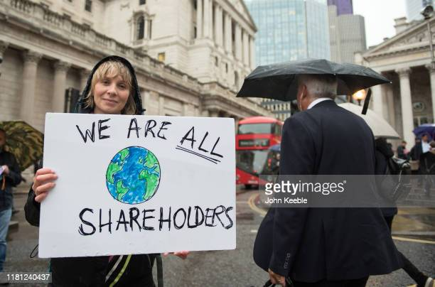 An Extinction Rebellion protester holds up a placard saying We are all shareholders as they block the roads outside the Bank of England on October 14...