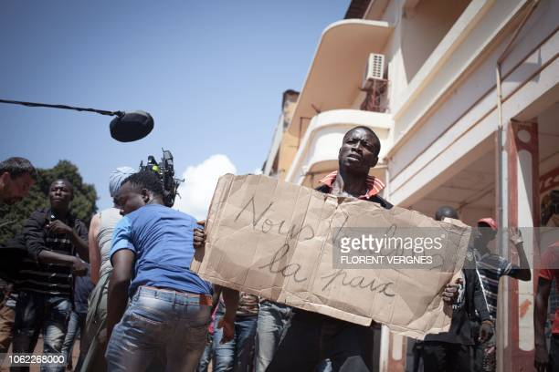 An extra from the film 'Camille' based on the life of French photojournalist Camille Lepage holds a sign reading 'we want peace' during a...