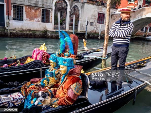 une paire extraordinaire de masques sur une gondole traditionnelle pendant le carnaval de venise - carnaval de venise photos et images de collection