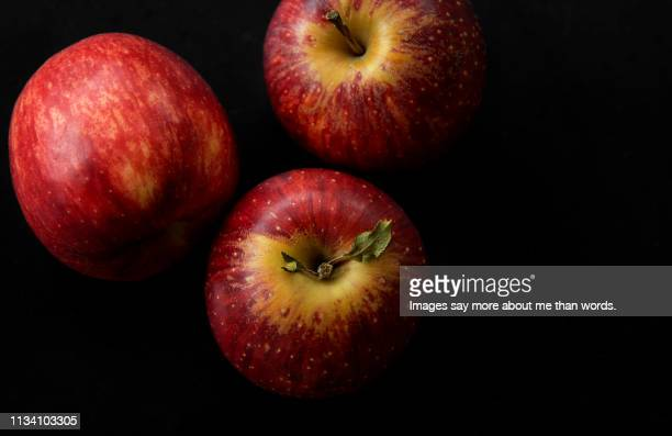 an extreme close up of three very red apples. still life. - 極端なクローズアップ ストックフォトと画像