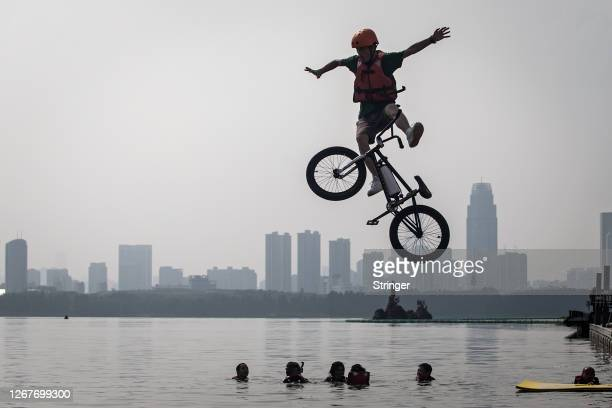 An extreme cycling enthusiast performs a stunt with a bicycle before falling into the East Lake in on August 22, 2020 in Wuhan, Hubei province,...