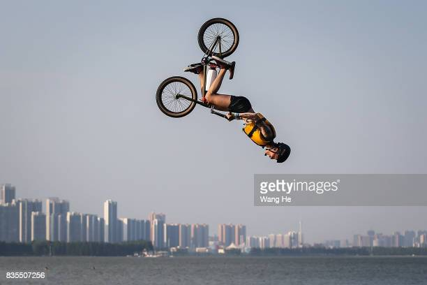 An extreme cycling enthusiast performs a stunt with a bicycle before falling into the East Lake on August 19 2017 in Wuhan Hubei province China This...