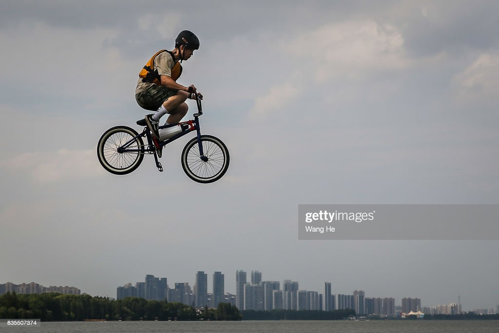 An extreme cycling enthusiast performs a stunt with a bicycle before falling into the East Lake on August 19, 2017 in Wuhan, Hubei province, China. This activity, which requires participants to ride their bikes and jump into the lake, attracts many extreme cycling enthusiasts from the city.