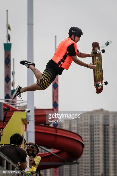 An extreme cycling enthusiast performs a stunt with a Skate before falling into the East Lake on August 18 2018 in Wuhan Hubei province China This...