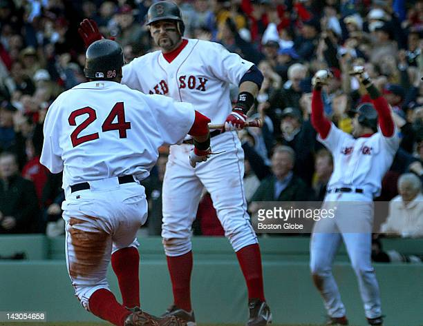 An exuberant Nomar Garciaparra at far right leads the cheers after he and Manny Ramirez at far left scored on David Ortiz's double in the eighth...