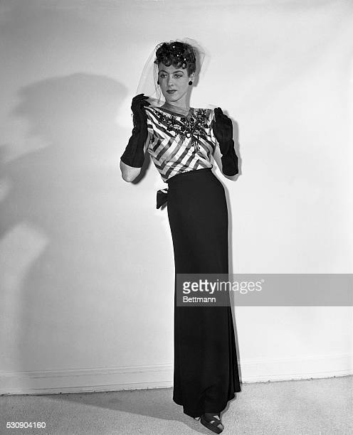 An eyecatching bodice of black and pink striped satin embroidered with jet tops the slim black crepe skirt of this Hattie Carnegie model The...
