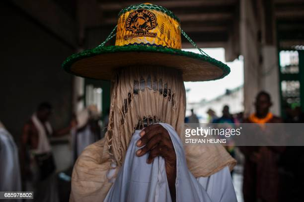 An Eyo masquerader looks on as he arrives at the Tafawa Balewa Square in Lagos on May 20 2017 The whiteclad Eyo masquerades represent the spirits of...