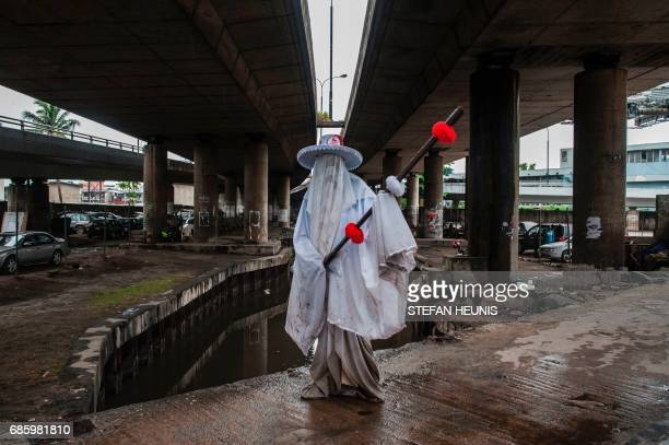 An Eyo masquerader poses under a bridge in the streets of Lagos on May 20 2017 during the Eyo festival The whiteclad Eyo masquerades represent the...