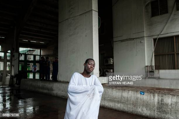 An Eyo masquerader poses without his costume at the Tafawa Balewa Square in Lagos on May 20 2017 The whiteclad Eyo masquerades represent the spirits...