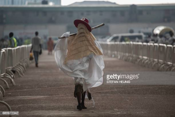An Eyo masquerader walks towards the Tafawa Balewa Square in Lagos on May 20 2017 The whiteclad Eyo masquerades represent the spirits of the dead and...