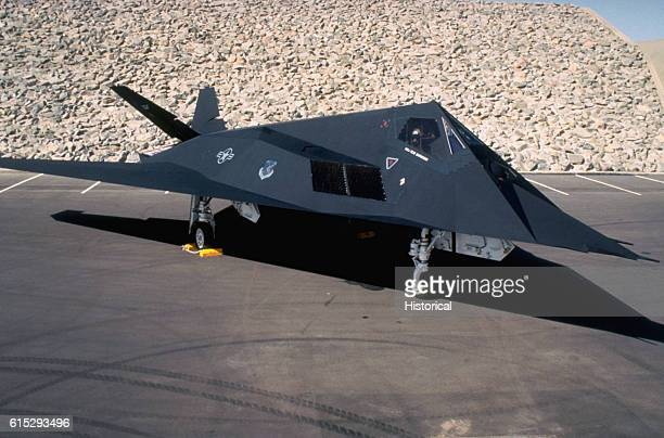 An F117A aircraft from the 37th Tactical Fighter Wing sits parked in front of a wall during Operation Desert Shield Saudi Arabia ca January 1991
