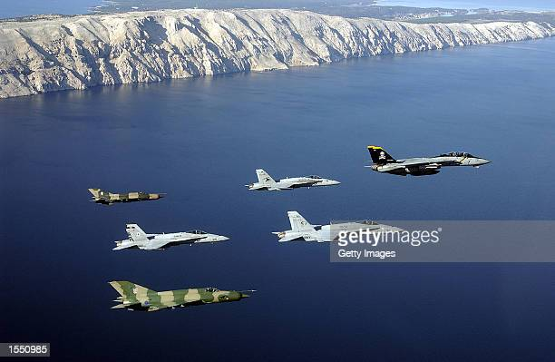 An F14 ''Tomcat'' fighter leads a formation comprised of F/A18 Hornet strike fighters October 29 2002 over Pula Croatia US Two Croat MiG21 Fishbed...
