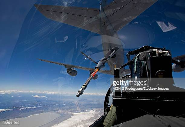 An F-15 Eagle pulls into pre-contact position behind a KC-135 Stratotanker during a training mission.