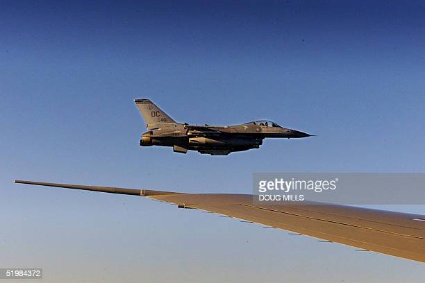 An F-16 fighter flies just off the wing of Air Force One on a flight back to Washington 11 September 2001. Bush returned to the White House where he...
