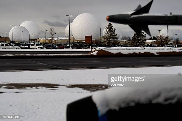 An F16 Fighting Falcon display with the large radomes at Buckley Air Force Base rising behind it They are large geodesic domes that are used to...