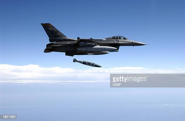 An F16CJ from the 78th Fighter Squadron at Shaw Air Force Base South Carolina flies over the Eglin Land Range as the pilot releases a GBU31 2000...