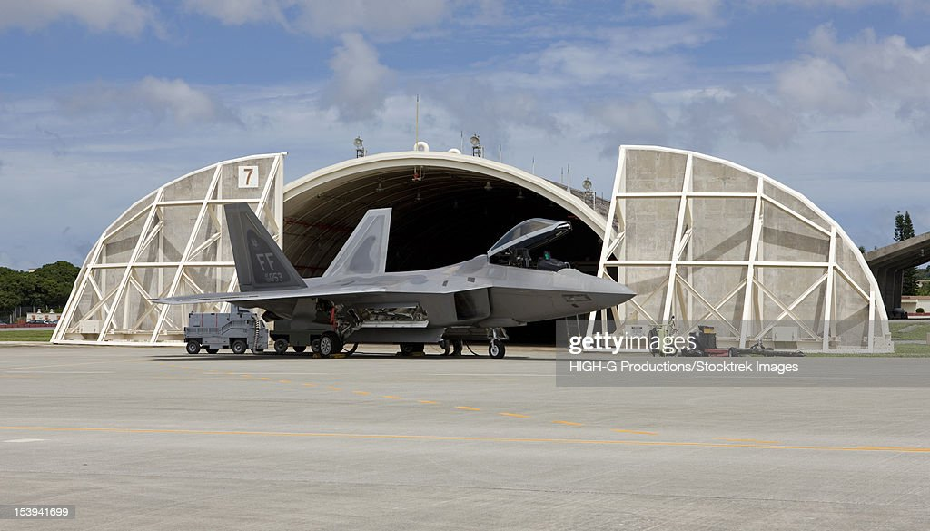 An F-22 Raptor from Langley Air Force Base, Virginia, sits in front of a hardened aircraft shelter at Kadena Air Base, Okinawa. : Stock Photo