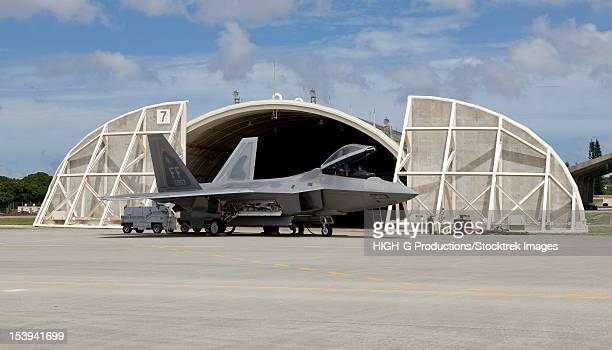 An F-22 Raptor from Langley Air Force Base, Virginia, sits in front of a hardened aircraft shelter at Kadena Air Base, Okinawa.