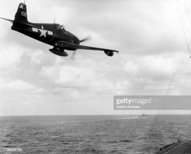 An F6F Hellcat night fighter flies past the US Navy aircraft carrier USS Hornet during strikes on Formosa October 12 1944