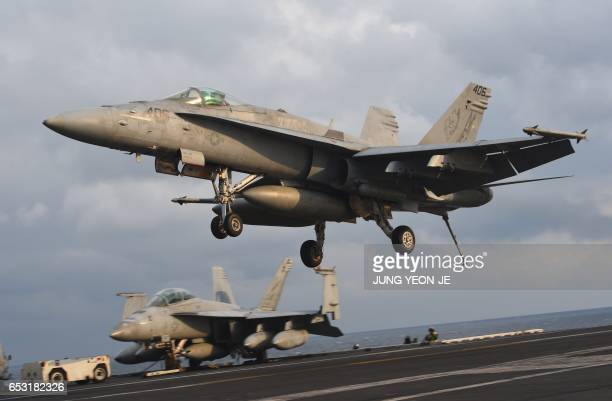 An F/A18 fighter lands on the deck of the Nimitzclass aircraft carrier USS Carl Vinson during a South KoreaUS joint military cxercise in seas east of...