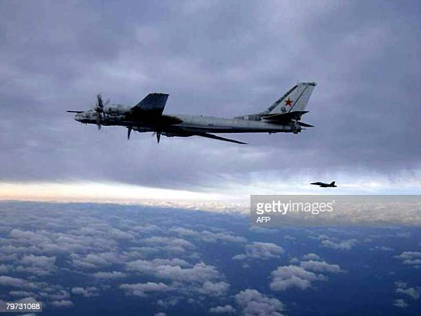 An F/A18 Hornet from Carrier Air Wing 11 embarked aboard the aircraft carrier USS Nimitz escorts a Russian Tu95 Bear long rang bomber aircraft on...
