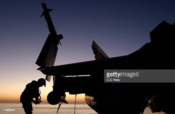 """An F/A-18 """"Hornet"""" pilot inspects his aircraft prior to flight operations October 23, 2001 in support of Operation Enduring Freedom."""