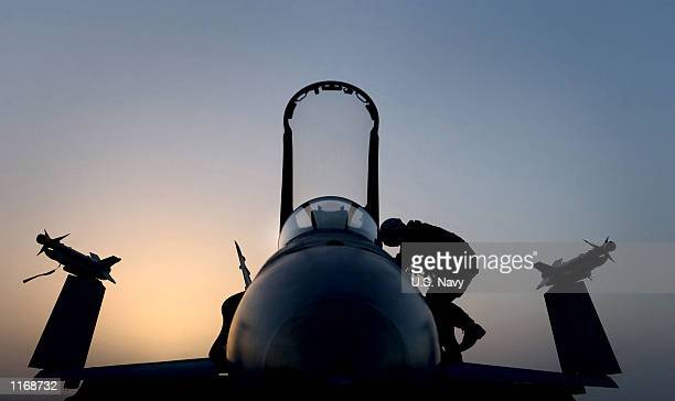 """An F/A-18 """"Hornet"""" strike fighter pilot exits his aircraft after returning from flight operations over Afghanistan October 16, 2001 aboard the..."""
