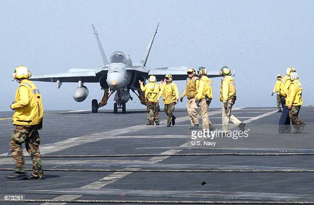 """An F/A-18 """"Hornet"""" taxies out of the landing area to make the flight deck ready for the next aircraft landing November 21, 2001 aboard the USS Kitty..."""