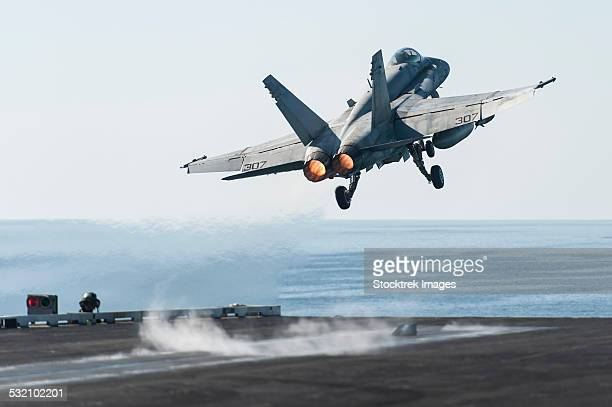 An F/A-18C Hornet launches from the flight deck of USS Harry S. Truman.