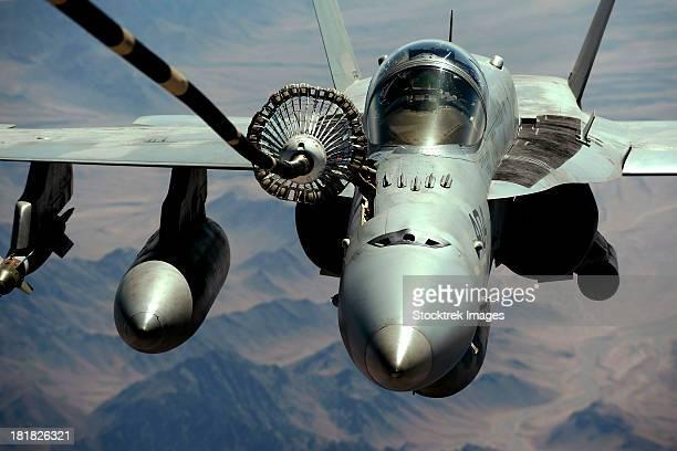 An F/A-18C Hornet receives fuel from the drogue of a KC-10 Extender.