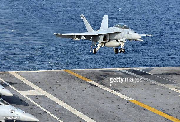 An F/A18E Super Hornet lands on the deck of the USS George Washington during a joint Navy exercise with South Korea in the Yellow sea on November 29...