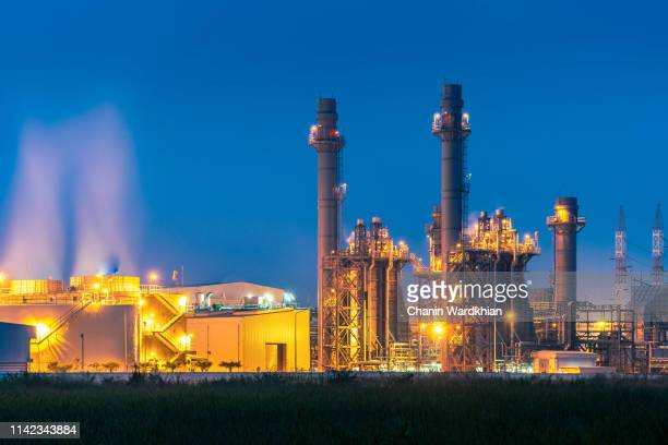 an factory with illuminated steam at night - smog china stock-fotos und bilder