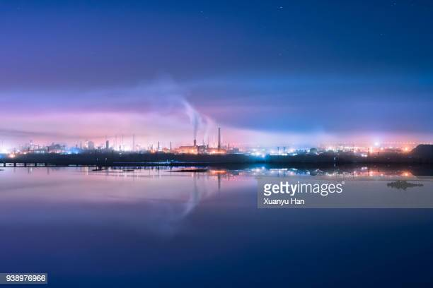 An factory with illuminated steam at night.