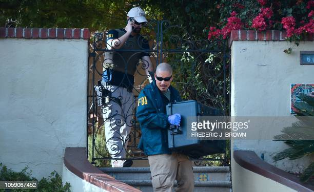 An FBI agent carries a case from the home of Los Angeles Councilman Jose Huizar in Los Angeles on November 7 2018 The FBI served sealed warrants at...