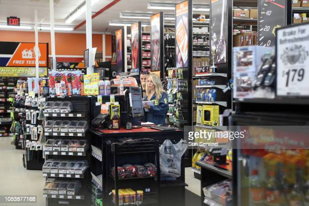 An FBI agent examines a computer at the AutoZone store on State Road 7 in Plantation where Cesar Sayoc Jr of Aventura was arrested on Friday Oct 26...