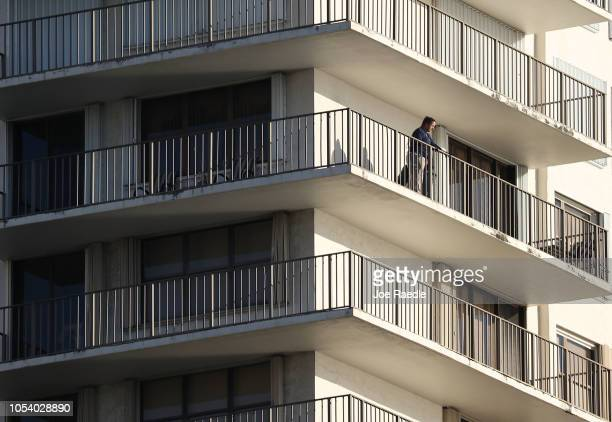 An FBI Agent looks out from a balcony of a condo in the building that has a possible connection to alleged bomber Cesar Sayoc and his mother on...