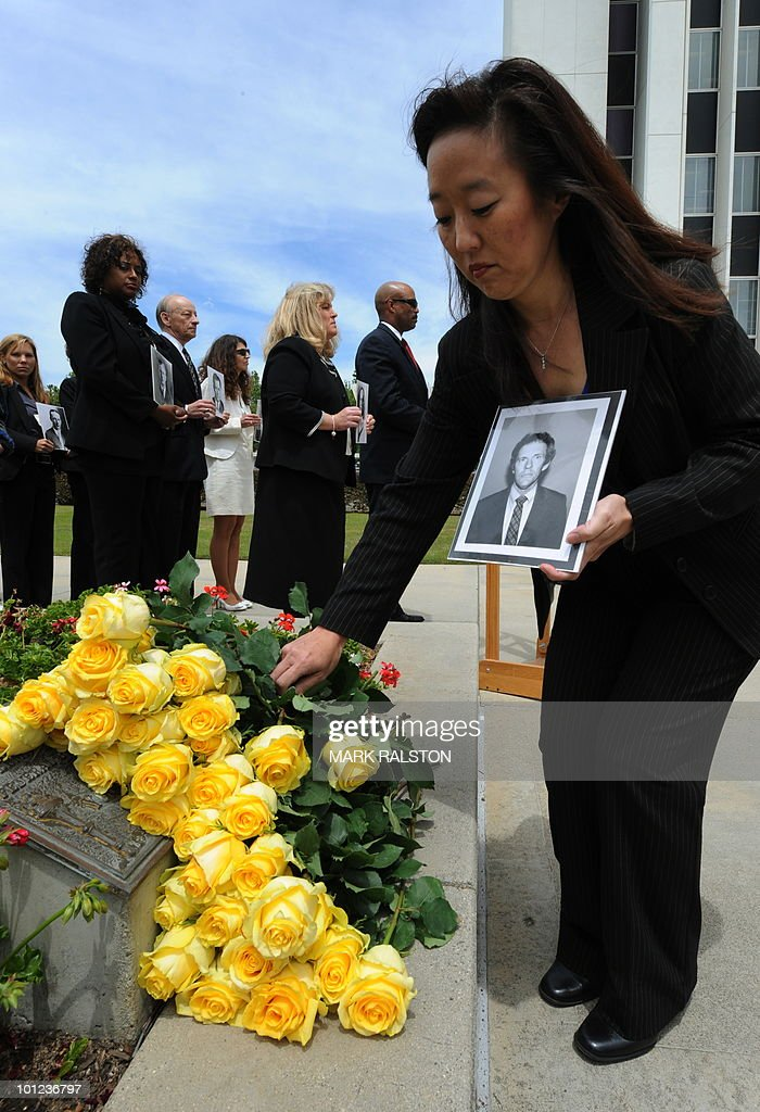An FBI agent places a flower on a memorial as other agents hold photos of deceased colleagues during a memorial service for Special Agents and their law enforcement and military colleagues killed in the line of duty at the Federal Building in Los Angeles on May 28, 2010. Memorial Day, which was formerly known as Decoration Day, commemorates US men and women who died while in the service to their country and was first enacted to honor Union soldiers of the American Civil War. AFP PHOTO/Mark RALSTON