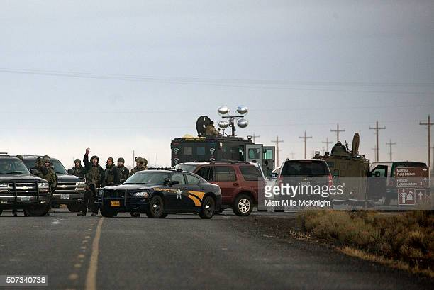 An FBI agent signals after a road block was moved allowing media to gather closer to the headquarters building at the Malheur National Wildlife...