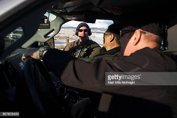 An FBI agent speaks with Burns Paiute Tribal Police outside the FBI command headquarters at Burns Municipal Airport January 30 2016 in Burns Oregon...