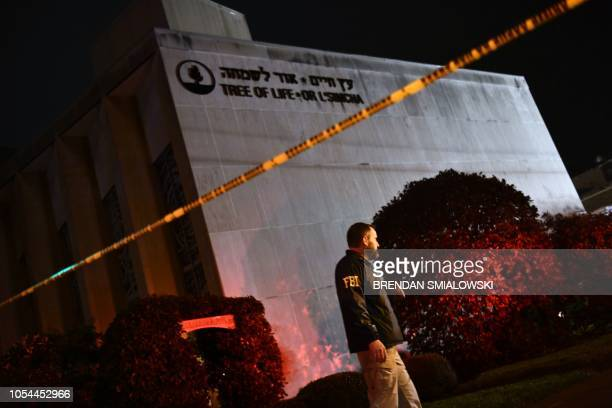 TOPSHOT An FBI agent stands behind a police cordon outside the Tree of Life Synagogue after a shooting there left 11 people dead in the Squirrel Hill...