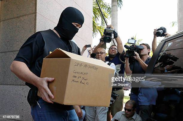 An FBI agent wearing a mask carries a box from the headquarters of CONCACAF after it was raided on May 27 2015 in Miami Beach Florida The raid is...