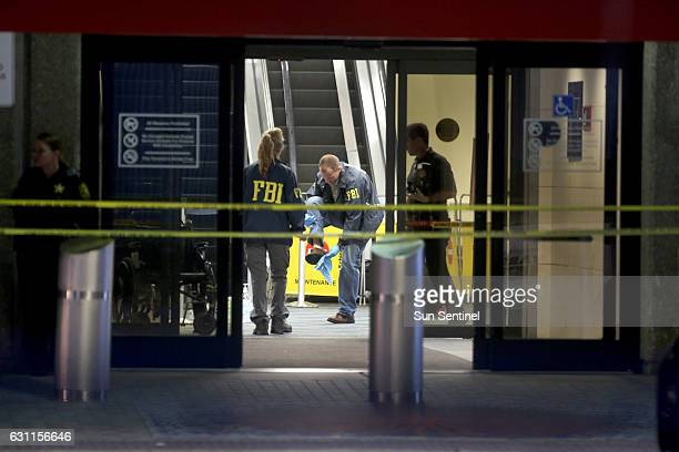 An FBI agent wipes off his shoe while working the crime scene as investigators continue their work in Terminal 2 at Fort Lauderdale International...