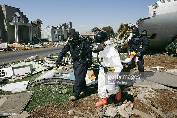 An FBI Hazardous Materials Team member in white and two members of the US Army Civil Support Team search for hazards during an exercise simulating...