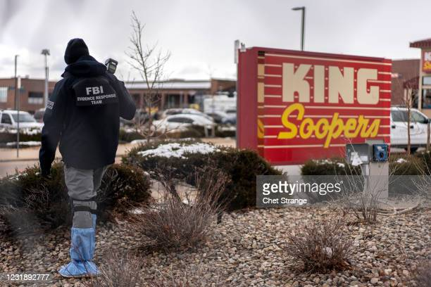 An FBI investigations officer from the evidence response team takes photographs of the crime scene the day after a gunman opened fire at a King...