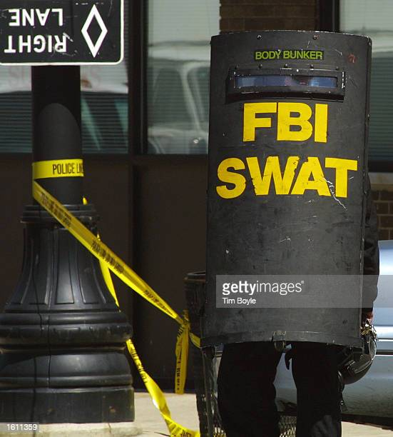 An FBI SWAT member is seen on the street near an apartment building August 28 2001 south of downtown Chicago A police officer was shot and held...